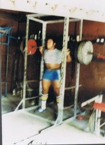 A rather old photograph converted from a Polaroid print, the author's son Kevin prepares for his junior season of college football in the garage gym, using a power rack fabricated by the author. Just as it is, or should be in the sport of powerlifting, there is a season and time in each season to vary resistance and reps in preparation for competition. Here he is in the midst of a 20-30 reps set with 425 pounds