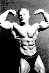 "This photo of the late Tony Pandolfo was taken when he was sixty years of age. Always in great physical condition, he inspired bodybuilders and lifters in the entire New York Metropolitan area to train hard and consistently. Tony was the sparkplug, and owner of the local storefront gym, that rounded up our group of guys who competed in various Odd Lift Contests in the New York City, and often beyond, areas. Typical for the era, he trained on the basic movements including the squat, bench press, and deadlift, and was every bit as strong as he was ""well built."" Tony won many physique titles, including his class at one of the Mr. America Contests but his legacy is one that most importantly includes the time and expertise he gave to so many others whom he trained for contests, and nurturing beginning trainees and lifters."